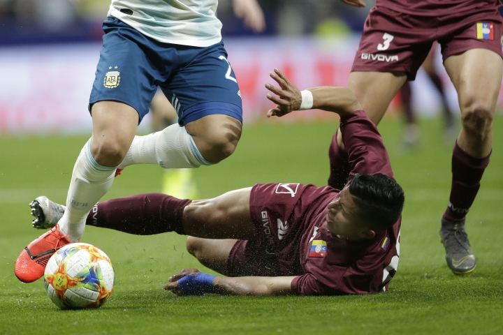 Venezuela's Ronald Hernandez, on the ground, fights for the ball with Argentina's Lautaro Martinez, left, during an international friendly soccer match between Argentina and Venezuela at Wanda Metropolitano stadium in Madrid, Spain, Friday, March 22, 2019. (AP Photo/Bernat Armangue)