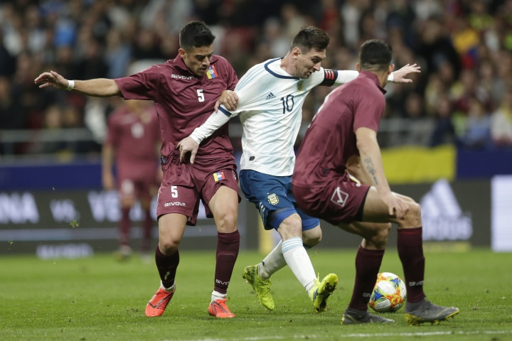 Argentina's Lionel Messi, center, fights for the ball with Venezuela's Junior Moreno, left, and Yordan Osorio, right, during an international friendly soccer match between Argentina and Venezuela at Wanda Metropolitano stadium in Madrid, Spain, Friday, March 22, 2019. (AP Photo/Bernat Armangue)