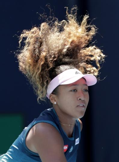 Naomi Osaka, of Japan, follows through on a serve to Yanina Wickmayer, of Belgium, during the Miami Open tennis tournament, Friday, March 22, 2019, in Miami Gardens, Fla. (AP Photo/Lynne Sladky)