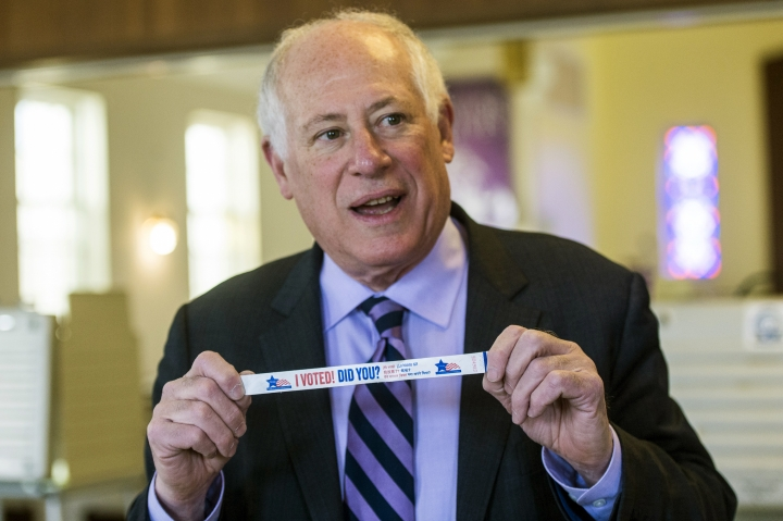 "FILE--In this March, 2018 file photo, Former Illinois governor and now Democratic Attorney General candidate Pat Quinn sports one of his famous purple striped ties as he holds up an ""I Voted"" wrist band after voting in Chicago. Gubernatorial fashion in Illinois gets a lot of attention. Quinn had a ""lucky"" purple striped tie, more than one, as it turned out. (Tyler LaRiviere/Chicago Sun-Times via AP, File)"