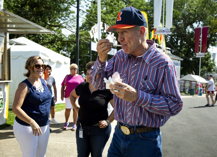 FILE--In this Aug. 9, 2018, file photo, Illinois Gov. Bruce Rauner eats strawberry ice cream while walking on the Illinois State Fairgrounds after officially opening the 2018 Illinois State Fair in Springfield, Ill. Gubernatorial fashion in Illinois gets a lot of attention. Rauner eschewed neckties with suits, wore big belt buckles, plaid shirts with rhinestone snaps, and a leather vest while astride his motorcycle. (Rich Saal /The State Journal-Register via AP, File)
