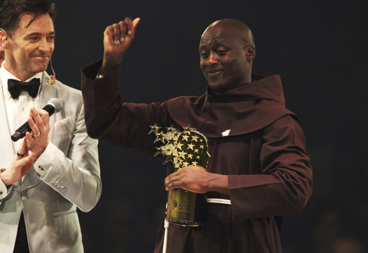 Kenyan teacher Peter Tabichi, right, reacts near actor Hugh Jackman, after winning the $1 million Global Teacher Prize in Dubai, United Arab Emirates, Sunday, March 24, 2019. Tabichi is a science teacher who gives away 80 percent of his income to the poor in the remote Kenyan village of Pwani. (AP Photo/Jon Gambrell)