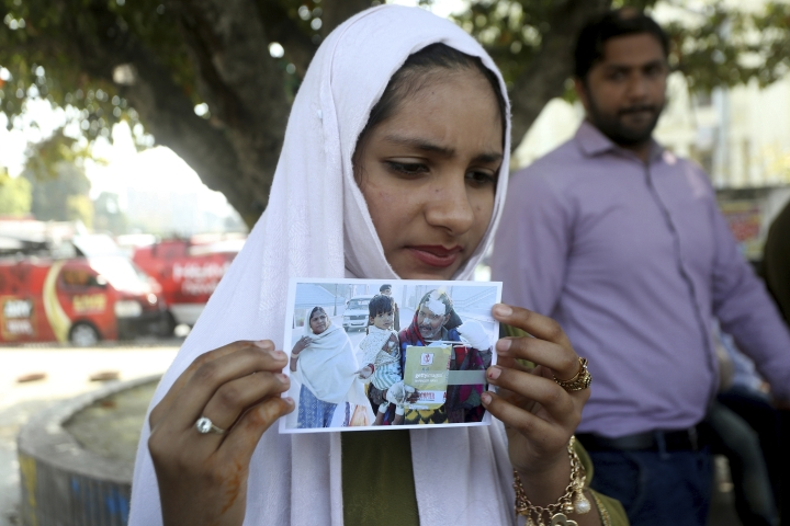 Aqsa Ali shows a picture of her father Shaukat Ali who was injured in a 2007 train explosion in India, during a protest in Lahore, Pakistan, Monday, March 25, 2019. Family members of Pakistanis killed and injured in an Indian train explosion are protesting an Indian court's acquittal of four Hindus charged with triggering the blasts 12 years ago, which killed 68 passengers. (AP Photo/K.M. Chaudary)