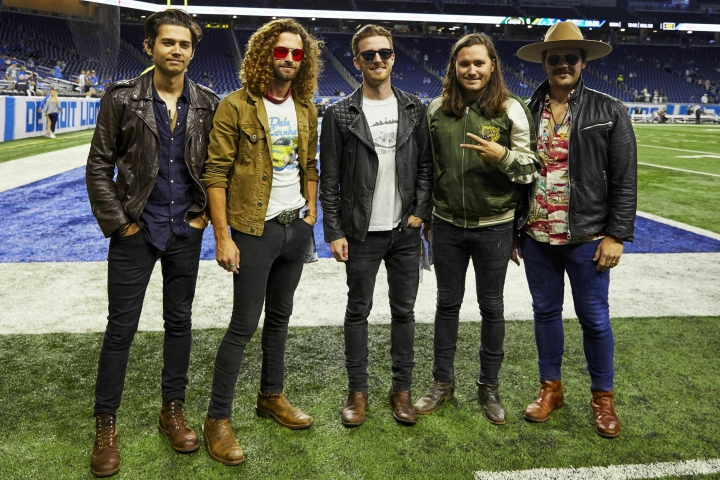"""FILE - This Sept. 10, 2018 file photo shows members of the band LANCO on the field before a NFL football game between the Detroit Lions and the New York Jets in Detroit. The Academy of Country Music named LANCO as best new group of the year. The group of five released their first album """"Hallelujah Nights"""" last year on Arista Nashville. (AP Photo/Rick Osentoski, File)"""