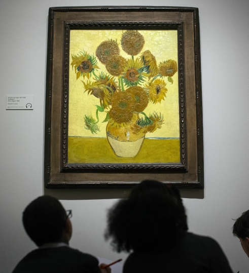 School children look at 'Sunflowers' (1888) by Vincent van Gogh during the preview for the upcoming Van Gogh and Britain exhibition at Tate Britain, in London, Monday March 25, 2019. The Van Gogh and Britain exhibition takes a new look at the artist through his relationship with Britain, and how he was inspired by British art, literature and culture. (Victoria Jones/PA via AP)