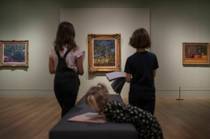 Children look at 'Trees in the Garden in Front of the Entrance to Saint-Paul Hospital' (1889) by Vincent van Gogh during the preview for the upcoming Van Gogh and Britain exhibition at Tate Britain in London, Monday March 25, 2019. The Van Gogh and Britain exhibition takes a new look at the artist through his relationship with Britain, and how he was inspired by British art, literature and culture. (Victoria Jones/PA via AP)