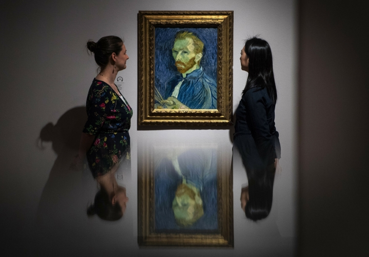 Staff members look at 'Self-Portrait' (1889) by Vincent van Gogh during the preview for the upcoming Van Gogh and Britain exhibition at Tate Britain, London, Monday March 25, 2019. The Van Gogh and Britain exhibition takes a new look at the artist through his relationship with Britain, and how he was inspired by British art, literature and culture. (Victoria Jones/PA via AP)