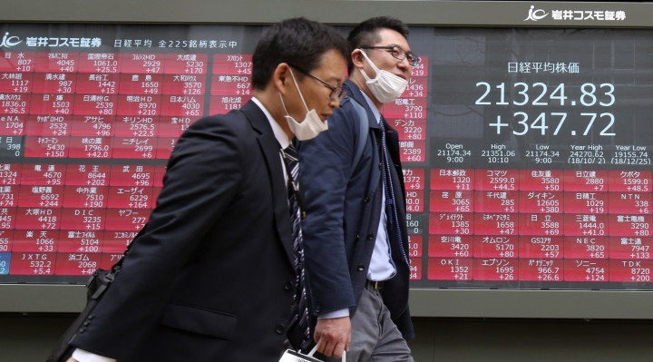 People walk by an electronic stock board of a securities firm in Tokyo, Tuesday, March 26, 2019. Asian stock prices rebounded Tuesday after global markets slid on worries about U.S. and European economic growth. (AP Photo/Koji Sasahara)