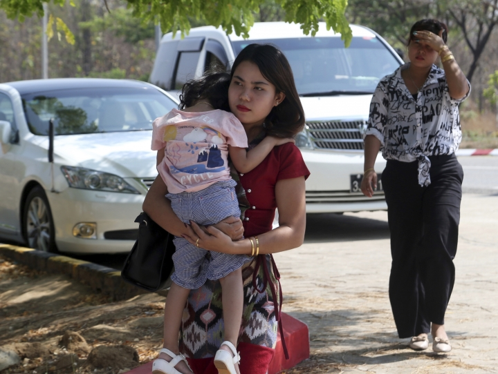 Chit Su Win, wife of Reuters journalist Kyaw Soe Oo, carries her daughter on arrival at the Supreme Court in Naypyitaw, Myanmar, Tuesday, March 26, 2019. Myanmar Supreme Court is expected to rule on appeal to overturn conviction of two Reuters journalists sentenced to seven years in prison on charges of violating Myanmar's Official Secrets Act. (AP Photo/Aung Shine Oo)