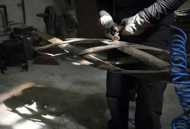 Artisan Devon Dixon smooths out imperfections on a bronze column as work continues on a permanent memorial to the victims of the 2013 Boston Marathon bombings, Tuesday, March 26, 2019, at a foundry in Chelsea, Mass. The long-awaited monuments of bronze, granite and lighted glass won't be ready in time for this year's race on April 15. (AP Photo/Elise Amendola)