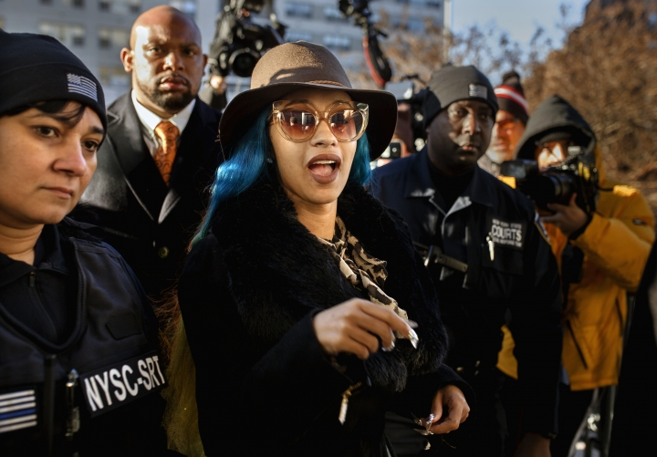 """FILE - This Dec. 7, 2018 file photo shows Rapper Cardi B, center, arriving at Queens County Criminal Court in New York on charges related to a brawl at a New York strip club. Cardi B is trying to clarify herself after a video surfaced online where the rapper said she drugged and robbed men for money. The Grammy winner posted a statement Tuesday, March 26, 2019, on Instagram that she had """"very limited options"""" and needed to do anything to """"survive."""" The former stripper says she wasn't trying to glorify her actions, but felt it was necessary at the time. (AP Photo/Andres Kudacki, File)"""