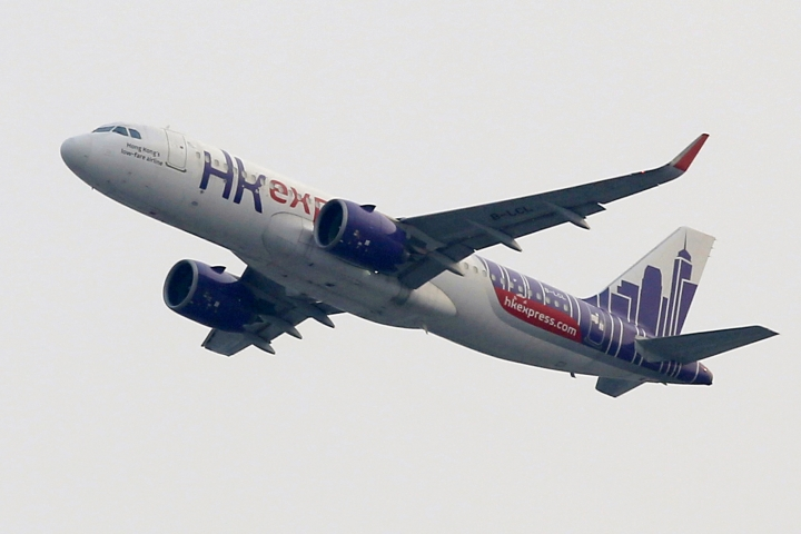 In this March 26, 2019 photo, a Hong Kong Express Airways passenger aircraft takes off from at the Hong Kong International Airport. Cathay Pacific Airways is acquiring Hong Kong-based budget airline HK Express. Cathay said Wednesday, March 27, 2019, it will pay 4.93 billion Hong Kong dollars ($628 million) for HK Express. It said the acquisition will retain its identity as a separate brand and be operated as a low-cost carrier. (AP Photo/Kin Cheung)