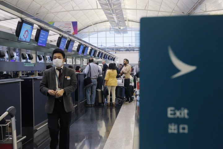 In this March 26, 2019 photo, passengers wait at the check-in counter of Cathay Pacific Airways at the Hong Kong International Airport. Cathay Pacific Airways is acquiring Hong Kong-based budget airline HK Express. Cathay said Wednesday, March 27, 2019, it will pay 4.93 billion Hong Kong dollars ($628 million) for HK Express. It said the acquisition will retain its identity as a separate brand and be operated as a low-cost carrier. (AP Photo/Kin Cheung)