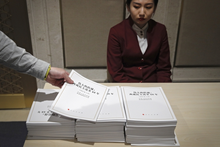An attendant looks as a journalist take a copy of a report on Tibet before a press conference by Tibet Executive vice governor Norbu Dondrup at the State Council Information Office in Beijing, Wednesday, March 27, 2019. Chinese officials responsible for Tibet are praising development in the Himalayan region in the 60 years since the suppression of an uprising against Beijing's rule. Executive vice governor Norbu Dondrup on Wednesday reviewed gains in the economy, health care and education since 1959 and castigated the self-declared government-in-exile established by Buddhist leader the Dalai Lama as illegitimate. The now-83-year-old Dalai Lama fled to India after the uprising was suppressed. (AP Photo/Andy Wong)