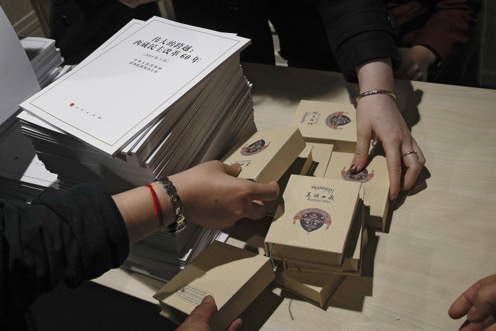 Journalists take souvenirs provided by a Tibetan official on display next to copies of a report on Tibet before a press conference by Tibet Executive vice governor Norbu Dondrup at the State Council Information Office in Beijing, Wednesday, March 27, 2019. Chinese officials responsible for Tibet are praising development in the Himalayan region in the 60 years since the suppression of an uprising against Beijing's rule. Executive vice governor Norbu Dondrup on Wednesday reviewed gains in the economy, health care and education since 1959 and castigated the self-declared government-in-exile established by Buddhist leader the Dalai Lama as illegitimate. The now-83-year-old Dalai Lama fled to India after the uprising was suppressed. (AP Photo/Andy Wong)