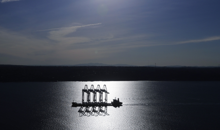 FILE- In this March 5, 2019, file photo the Zhen Hua 31 heavy-lift ship carrying four super-post-Panamax container cranes is silhouetted by the sun as it sails into Commencement Bay in Tacoma, Wash. On Wednesday, March 27, the Commerce Department reports on the U.S. trade gap for January. (AP Photo/Ted S. Warren, File)