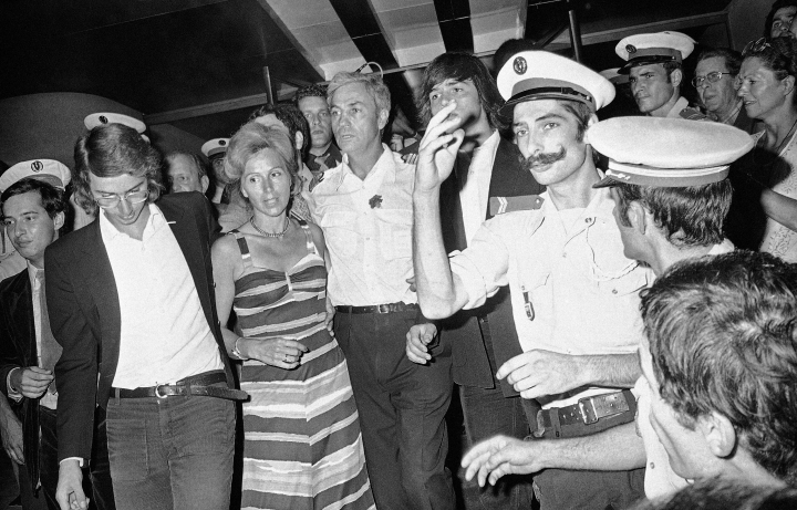 FILE - In this July 5, 1976 file photo, head pilot Michel Bacos, center left, is reunited with his wife, 2nd left, and son at Orly Airport near Paris, France, as the 12-member crew of the hijacked Air France Airbus jetliner and 14 passengers return home from Tel Aviv after a week-long stay at Entebbe Airport in Uganda. The French pilot of the Air France plane hijacked to Uganda's Entebbe airport in 1976, in which 110 hostages were freed by Israeli commandos, has died at the age of 95. (AP Photo, File)