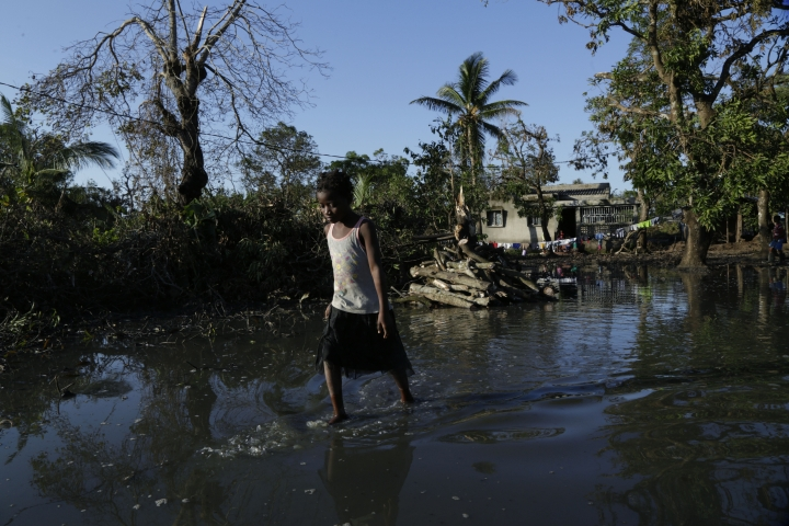 FILE - In this Tuesday March 26, 2019 file photo, a young girl walks through flood waters near Beira, Mozambique. Beira's mayor Davis Simango dreamed about protecting his people from climate change with much of the city being below sea level on a coastline that experts call one of the world's most vulnerable to global warming's rising waters. (AP Photo/Themba Hadebe, File)