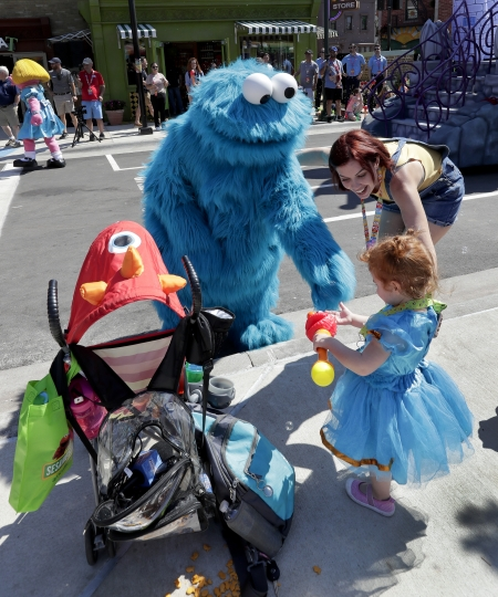In this Tuesday, March 26, 2019 photo, the Cookie monster greets guests during a preview day at SeaWorld Orlando opening of Sesame Street land in Orlando, Fla., an addition to central Florida's theme park landscape aimed at young families. (AP Photo/John Raoux)