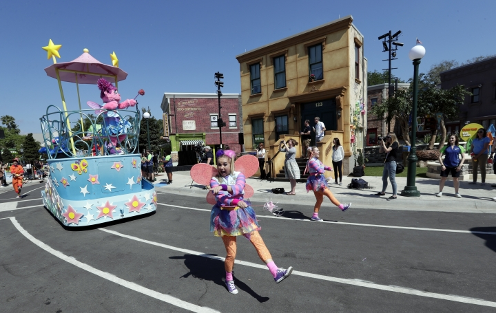 In this Tuesday, March 26, 2019 photo, performers and characters take part in a parade during a preview day at SeaWorld Orlando opening of Sesame Street land in Orlando, Fla., an addition to central Florida's theme park landscape aimed at young families. (AP Photo/John Raoux)