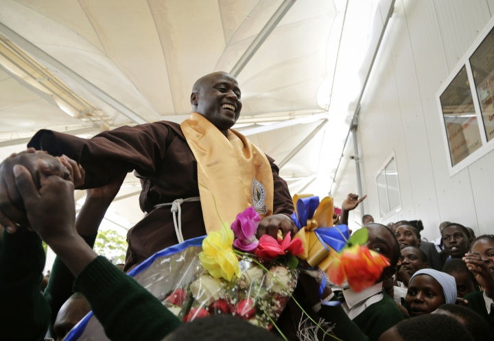 Kenyan teacher Peter Tabichi is welcomed back by the students from his school upon his arrival at the airport in Nairobi, Kenya Wednesday, March 27, 2018. Tabichi, who won the $1 million Global Teacher Prize, returned home to pomp and pageantry and the Franciscan friar has a message for Africa: Invest in youth. (AP Photo/Khalil Senosi)
