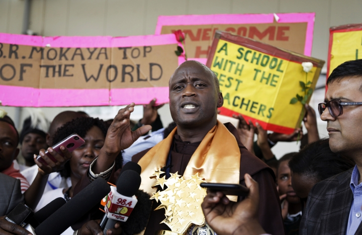 Kenyan teacher Peter Tabichi speaks to the media after being welcomed back by the students from his school upon his arrival at the airport in Nairobi, Kenya Wednesday, March 27, 2018. Tabichi, who won the $1 million Global Teacher Prize, returned home to pomp and pageantry and the Franciscan friar has a message for Africa: Invest in youth. (AP Photo/Khalil Senosi)