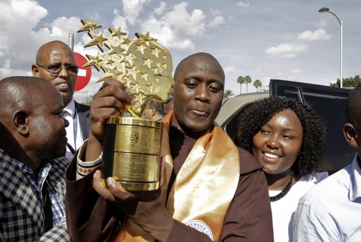 Kenyan teacher Peter Tabichi carries his trophy as he arrives back at the airport in Nairobi, Kenya Wednesday, March 27, 2018. Tabichi, who won the $1 million Global Teacher Prize, returned home to pomp and pageantry and the Franciscan friar has a message for Africa: Invest in youth. (AP Photo/Khalil Senosi)