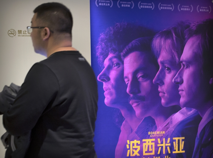 "A customer walks past a movie poster for the film ""Bohemian Rhapsody"" at a movie theater in Beijing, Wednesday, March 27, 2019. Moviegoers in China say the version of the ""Bohemian Rhapsody"" shown in Chinese theaters erases mentions of Freddie Mercury's sexuality. The biopic on the lead singer of the British rock band Queen omitted a same-sex kiss and lacked scenes in which Mercury reveals he's not straight and has AIDS. (AP Photo/Mark Schiefelbein)"