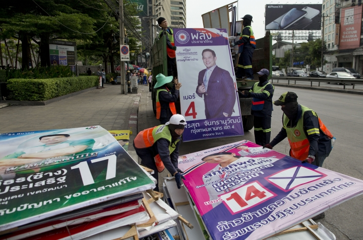 Workers load campaign billboards displayed to promote candidates for a general election into a truck in Bangkok, Thailand, Wednesday, March 27, 2019. The results of Sunday's general election will be formally announced on May 9. (AP Photo/Gemunu Amarasinghe)