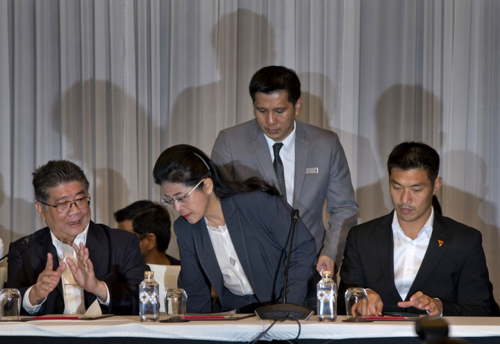 Pheu Thai party candidate for prime minister Sudarat Keyuraphan, center, takes her seat as Pheu Thai party Secretary General Phumtam Wechayachai, left and Future Forward party leader Thanathorn Juangroongruangkit, right are seated during signing of an agreement to work as a collation in Bangkok, Thailand, Wednesday, March 27, 2019. Seven political parties led by the flagship party loyal to former Prime Minister Thaksin Shinawatra have come together in a coalition to try to form Thailand's next government, even though the results of Sunday's general election will be formally announced only on May 9. (AP Photo/Gemunu Amarasinghe)