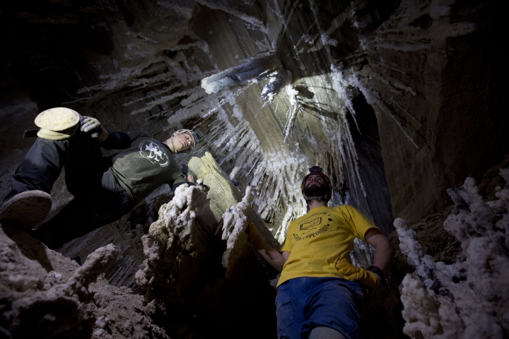 In this Wednesday, March 27, 2019 photo, Yoav Negev, and Boaz Langford, researchers at the Israel Cave Research Center of the Hebrew University of Jerusalem, examine salt stalactites hanging from the ceiling in the Malham cave at the Dead Sea in Israel. A recently completed survey of the cave determined the labyrinthine cavern stretches more than 10 kilometers (six miles) in length. (AP Photo/Ariel Schalit)