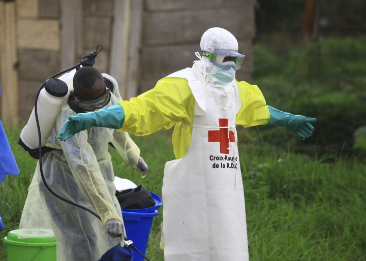 FILE - In this Sunday, Sept 9, 2018 file photo, a health worker sprays disinfectant on his colleague after working at an Ebola treatment center in Beni, eastern Congo. One-fourth of the people interviewed in eastern Congo last year believed Ebola wasn't real, according to a new study released Wednesday, underscoring the enormous challenges health care workers are now facing. (AP Photo/Al-hadji Kudra Maliro, File)