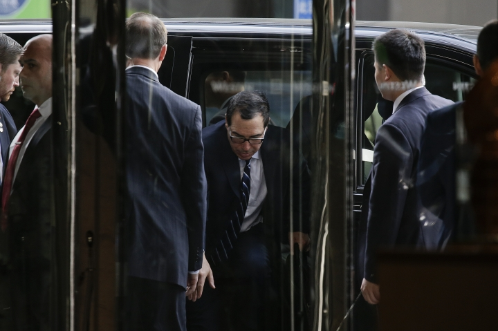 U.S. Treasury Secretary Steven Mnuchin, center, is surrounded by bodyguards as he steps out from a vehicle outside a hotel in Beijing, Thursday, March 28, 2019. Mnuchin and his Trade Representative Robert Lighthizer arrive at China's capital to hold a new round of high-level trade talks with China on March 28-29, start with a working dinner. (AP Photo/Andy Wong)