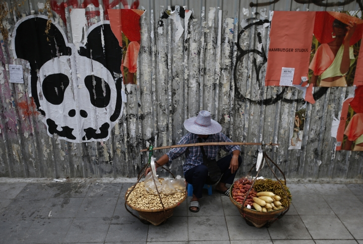 A street vendor waits for customers on a sidewalk in front of graffiti in Bangkok, Thailand Thursday, March 28, 2019. As Thais wait for official results of their general election, political parties led by one ousted from power in a military coup say they believe they have won enough seats to form the next government. (AP Photo/Sakchai Lalit)