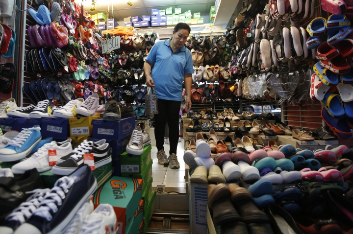 A Thai customer looks for shoes in Bangkok, Thailand, Thursday, March 28, 2019. As Thais wait for official results of their general election, political parties led by one ousted from power in a military coup say they believe they have won enough seats to form the next government.(AP Photo/Sakchai Lalit)
