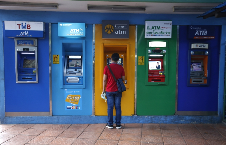 A Thai man withdraw money from automated teller machine Bangkok, Thailand Thursday, March 28, 2019. As Thais wait for official results of their general election, political parties led by one ousted from power in a military coup say they believe they have won enough seats to form the next government.(AP Photo/Sakchai Lalit)