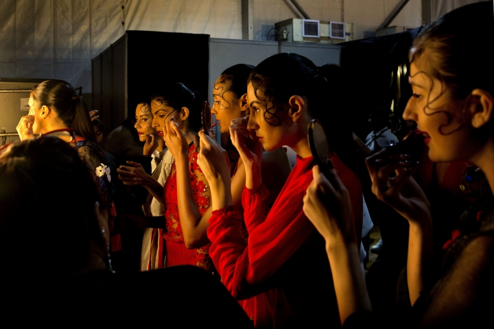 In this Wednesday, March 13, 2019, photo, models touch up their makeup before a show during the Lotus Makeup India Fashion Week, in New Delhi, India. It's fashion season in India's capital city with the country's top designers showcasing their latest collections to lure the rapidly growing domestic and export markets for Indian haute couture. (AP Photo/Manish Swarup)