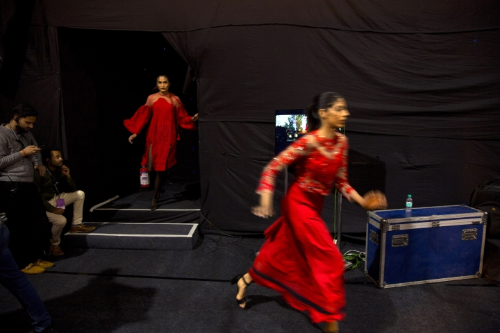 In this Wednesday, March 13, 2019, photo, models rush for a quick change of outfit in between a ramp walk during the Lotus Makeup India Fashion Week, in New Delhi, India. It's fashion season in India's capital city with the country's top designers showcasing their latest collections to lure the rapidly growing domestic and export markets for Indian haute couture. (AP Photo/Manish Swarup)