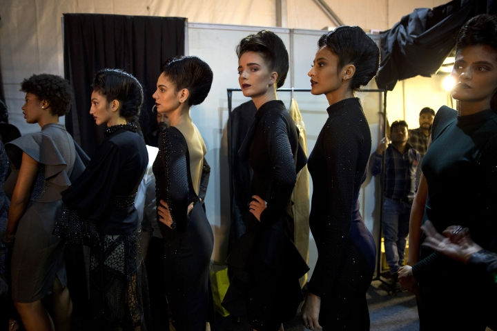 In this Saturday, March 16, 2019, photo, models line up backstage before the start of a catwalk during Lotus Makeup India Fashion Week, in New Delhi, India. It's fashion season in India's capital city with the country's top designers showcasing their latest collections to lure the rapidly growing domestic and export markets for Indian haute couture. (AP Photo/Manish Swarup)
