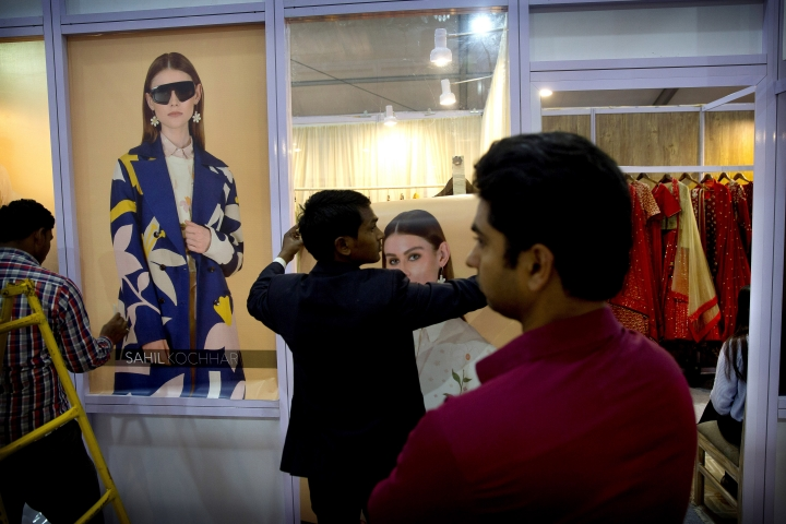 In this Wednesday, March 13, 2019, photo, workers put up posters of models outside a fashion designer's stall in an exhibition during Lotus Makeup India Fashion Week, in New Delhi, India. It's fashion season in India's capital city with the country's top designers showcasing their latest collections to lure the rapidly growing domestic and export markets for Indian haute couture. (AP Photo/Manish Swarup)