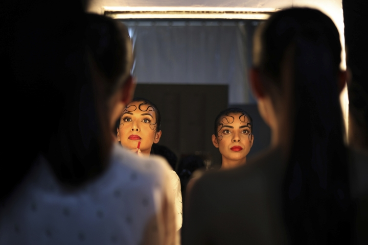 In this Wednesday, March 13, 2019, photo, models work on finishing touches before walking the ramp during Lotus Makeup India Fashion Week, in New Delhi, India. Organized by the Fashion Design Council of India, more than 100 of India's top names in fashion and 50 models from India and overseas participated in the Lotus Makeup India Fashion Week. (AP Photo/Manish Swarup)