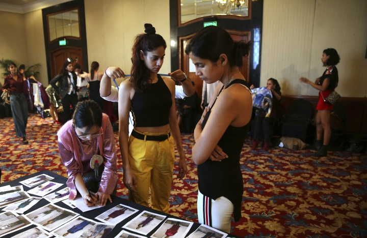 In this Monday, March 11, 2019, photo, a tailor takes measurements of a model as a woman scans photographs during a fitting session ahead of the Lotus Makeup India Fashion Week, in New Delhi, India. Organized by the Fashion Design Council of India, more than 100 of India's top names in fashion and 50 models from India and overseas participated in the five day Lotus Makeup India Fashion Week (AP Photo/Manish Swarup)