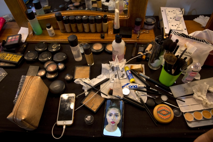 In this Thursday, March 14, 2019, photo, a photograph of an Indian model is seen on the mobile phone of a makeup artist at the main makeup room for models during Lotus Makeup India Fashion Week, in New Delhi, India. It's fashion season in India's capital, with the country's top designers showcasing their latest collections to lure the rapidly growing domestic and export markets for Indian haute couture. (AP Photo/Manish Swarup)