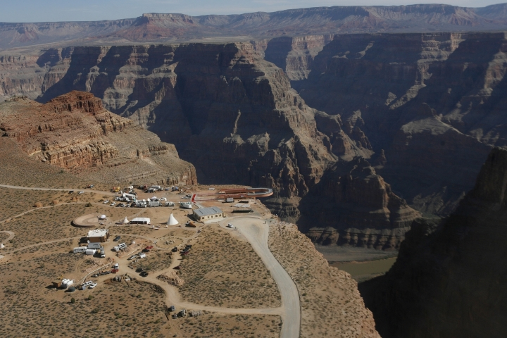 FILE - In this March 20, 2007, file photo, the Skywalk hangs over the Grand Canyon on the Hualapai Indian Reservation before its grand opening ceremony at Grand Canyon West, Ariz. Crews are searching for a tourist who slipped and fell over the edge of a Grand Canyon lookout on tribal land. The fall happened Thursday, March 28, 2019, morning on the Hualapai Tribe's reservation outside the boundaries of Grand Canyon National Park. (AP Photo/Ross D. Franklin, File)