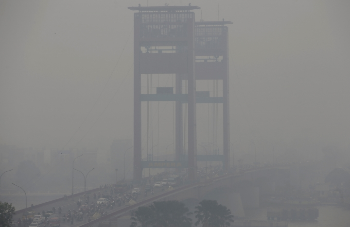 FILE - In this Sept. 19, 201, file photo, the vertical-lift Ampera Bridge spanning over the Musi River is shrouded by haze in Palembang, South Sumatra, Indonesia. Indonesia's air quality has deteriorated from among the cleanest in the world to one of the most polluted over the past two decades, shaving five years from life expectancy in some regions, researchers say. (AP Photo/Tatan Syuflana, File)