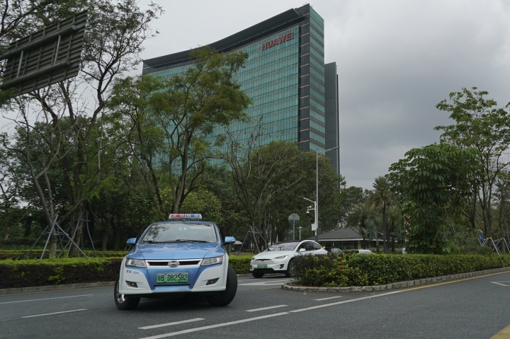 An electric taxi makes a U-turn in front of a Huawei office building in Shenzhen in south China's Guangdong province, Friday, March 29, 2019. Chinese tech giant Huawei said its 2018 sales surged above $100 billion, though sales of network equipment were flat amid U.S. warnings to other governments that its telecom technology is a security risk. (AP Photo/Dake Kang)