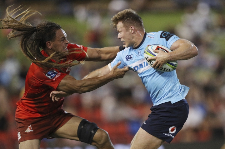 Dan Pryor, left, of the Sunwolves tries to tackle Cam Clark of the Waratahs during the Round 7 Super Rugby match between the New South Wales Waratahs and the Sunwolves at McDonald Jones Stadium in Newcastle, Australia Friday, March 29, 2019. (AAP Image/Paul Barkley)