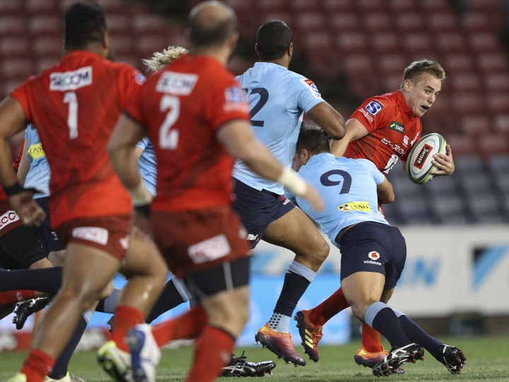 Hayden Parker, right, of the Sunwolves makes a break during the Round 7 Super Rugby match between the New South Wales Waratahs and the Sunwolves at McDonald Jones Stadium in Newcastle, Australia Friday, March 29, 2019. (AAP Image/Paul Barkley)