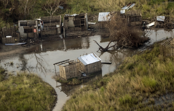 A man pushes his bicycle past submerged huts near Beira, Mozambique, Thursday, March 28, 2019. The first cases of cholera have been confirmed in the cyclone-ravaged city of Beira, Mozambican authorities announced on Wednesday, raising the stakes in an already desperate fight to help hundreds of thousands of people sheltering in increasingly squalid conditions. (AP Photo/Themba Hadebe)