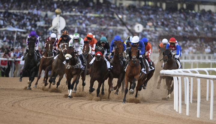 Horses gallop into the first turn in the $2.5 million Group 2 UAE Derby over 1900m in Dubai, United Arab Emirates, Saturday, March 30, 2019. (AP Photo/Martin Dokoupil)